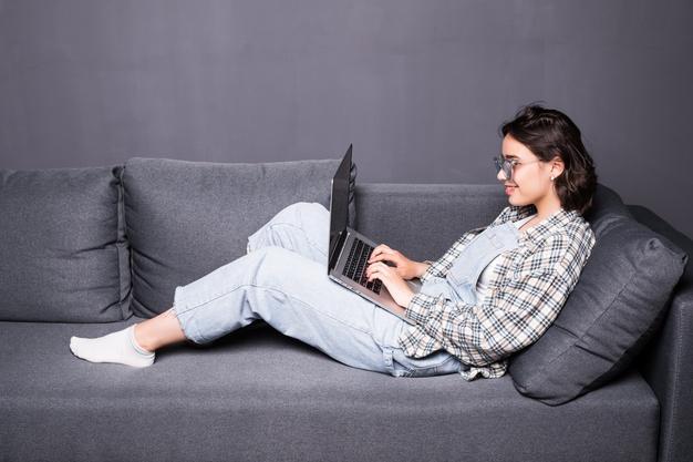 Γυναίκα ξαπλωμένη επάνω σε μαύρο καναπέ