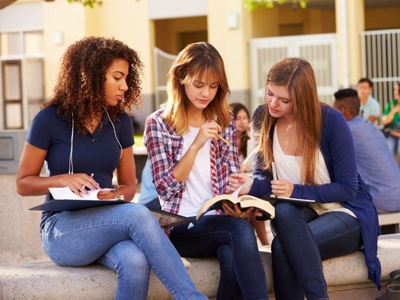Μαθήτριες μελετούν σχολικό βοήθημα πριν τις εξετάσεις